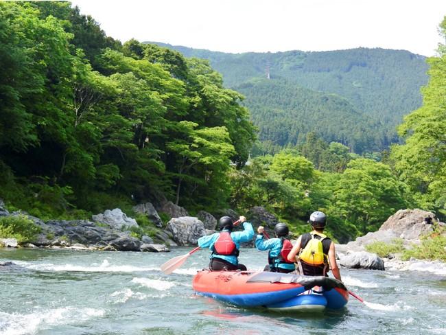 新緑の下、水しぶきを浴びて川を下るラフティング